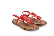 Sandalia de dedo con flores, de piel color rojo y brillantes en la pala. Piso de goma.