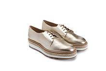 Zapato con cordones de piel metalizada platino. Vivo de esparto. Bajo microporoso. Piso de goma.