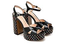Sandalia de charol negro y tachas multicolor. Plataforma 3cm y tacón 11cm. Piso de cuero.