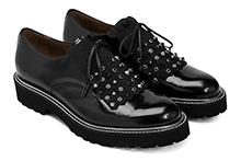 Zapato de piel negro, con cordones y flecos con tachas. Vivo plateado. Piso de goma.