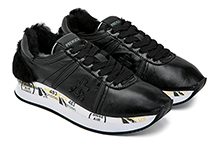 Zapatilla deportiva con cordones, en piel y mouton color negro. Piso de goma.