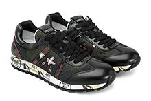Zapatilla deportiva con cordones, en mimetizado caqui, piel y mouton negro. Piso de goma.