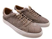 Zapato deportivo de cordones en serraje color visón. Piso grueso de goma blanca. Talonera blanca