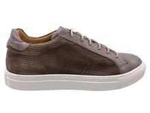 Zapato deportivo de cordones en piel de color visón. Piso grueso de goma blanca.