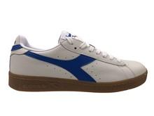 Deportiva en piel blanca con tira lateral azul claro. Piso de goma blanco.