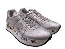 Deportiva en piel metalizada plata. Piso de goma. Altura total de 4 cm.