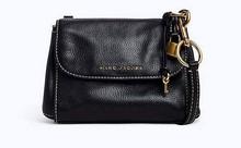 Mini bolso con solapa delantera en piel de color negro. Logo metálico. Asa larga.