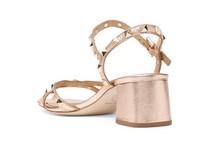 Sandalia de tiras en piel metalizada cobre. Adorno de tachas en todas las tiras. Tacón 4 cm.