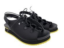 Sandalia en tejido negro con lazada en pala. Talonera descubierta. Piso de goma. Altura total 3 cm.