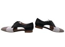 Zapato de cordones con aberturas laterales. Piel en colores negro, blanco, camel. Piso de cuero.