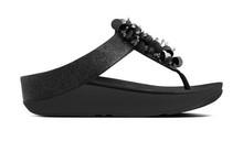 Sandalia de dedo con fantasía en la pala. Color negro. cuña de 4 cm. Piso de goma.