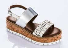 Sandalia de tiras en piel blanca y metalizada plata. Cuña de corcho. Piso de goma 5 cm. de altura.