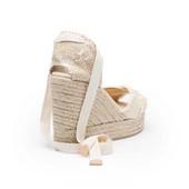 Alpargata tipo sandalia cruzada en lona deshilachada beige. Cuña de esparto de 8 cm. de altura.
