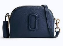 Mini bolso en piel azul marino. Asa larga de piel. Logo en la parte delantera grabado.