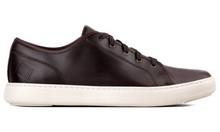 Zapato deportivo de cordones en piel de color marrón. Piso de goma de color blanco extralight.