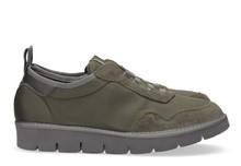 Zapatilla deportiva con cordones elásticos en ante y nylon de color gris. Piso de goma extralight.