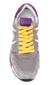 Deportiva de cordones en ante y nylon gris y lila. Cordones amarillos. Forro de piel. Piso de goma.