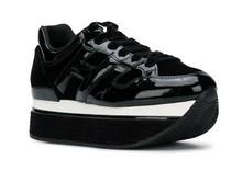 Deportiva de cordones en charol negro. Plataforma blanca y negra de 5 cm. de altura. Forro de piel.