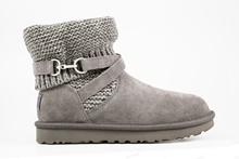 Botín en mouton gris con adorno metálico lateral. Caña en tejido gris. Forro de lana.