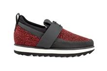 Zapato deportivo con cordones en negro y grabado rojo. Piso de goma blanco y negro. Altura 3 cm.