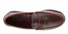 Mocasín con antifaz en piel engrasada de color tostado. Piso grueso de goma negra.