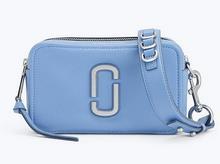 Mini bolso en piel de color azul medio. Adornos plateados. Cierre de cremallera. Bolsillo interior.