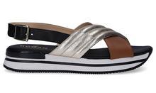 Sandalia cruzada en piel color tostado y metalizado oro. Piso grueso de goma blanco con raya negra.