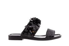 Sandalia de dos tiras en piel trenzada negra. Adorno de flor de piel en la pala. Piso de cuero.