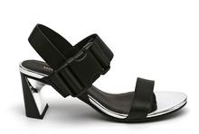 Sandalia de tiras en piel y tejido negro. Cierre delantero en velcro. Tacón negro y plata de 5 cm.