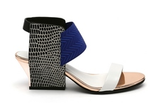 Sandalia de tiras en multimateriales blanco, azul y negro. Piso de cuero. Tacón ancho de 5 cm.