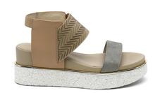 Sandalia de tiras en multimateriales beige y gris. Piso grueso de goma. Altura de la cuña 4 cm.