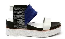 Sandalia de tiras en multimateriales azul, blanco y negro. Piso grueso de goma. Cuña de 4 cm. alt.