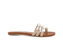Sandalia de dedo y tiras en tejido beige. Adornos de conchas beige. Planta de cuero. Tacón 1 cm.