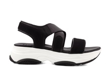 Sandalia en piel y tejido negro con elástico en el empeine. Piso grueso de goma de 4 cm. de altura.