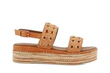 Sandalia en piel de color tostado. Con tachas doradas. Plataforma de yute fino de 5 cm. de altura.