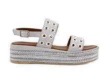 Sandalia en piel de color gris claro. Con tachas plateadas. Plataforma de yute fino de 5 cm.
