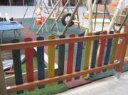 """Cerca de madeira com protector solar de cor """"parchis""""."""