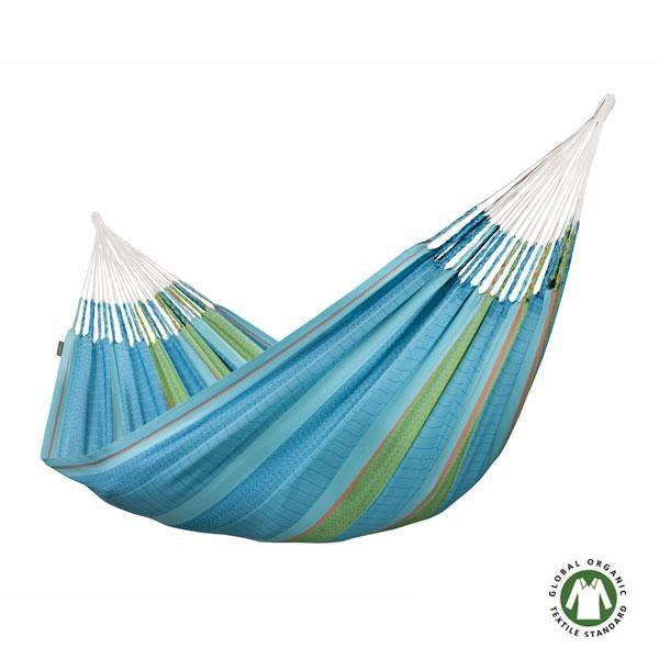 La Hamaca familiar Flora azul de algodón orgánico está tejida con algodón orgánico en jacquard, el hilo está trenzado de la forma tradicional colombiana utilizando en las puntas los Cadejos