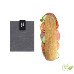 El portabocadillos negro Bloc'n'roll es un envoltorio reutilizable que te permite envolver y llevar tu bocadillos o piezas de fruta.