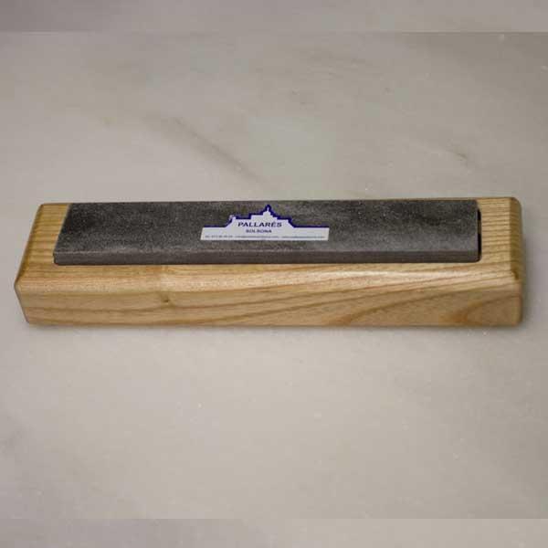 La piedra de afilar natural con soporte de madera de Cuchillos Pallarés: piedra natural de los Pirineos en forma rectangular es especial para el afilado de cuchillos. La piedra encaja en un bonito soporte de madera con patas antideslizantes.