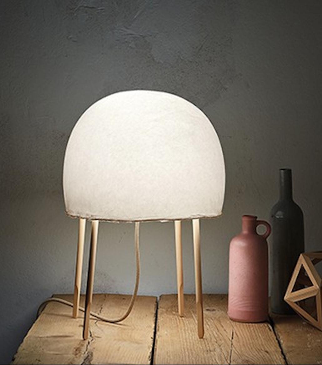 Lámpara de mesa Kurage, está confeccionada con con papel Washi y madera, ligera y cálida.