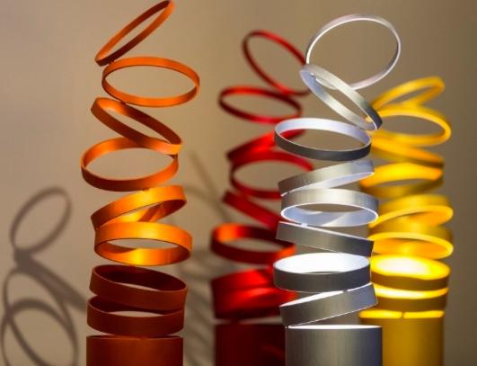 Lámpara nacida de un cilindro de aluminio, descomponiéndose en aros fijos en un punto y que parecen en movimiento que parecen bailar