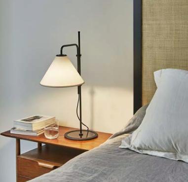 Lámpara funcional con estructura de varilla metálica en color negro y pantalla de tela en color beige o blanco regulable.