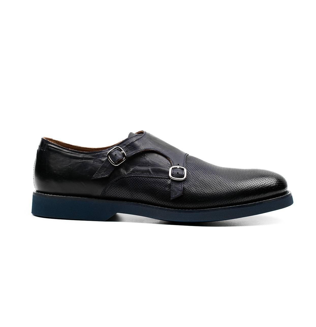 Zapato color azul marino con doble hebilla y combinación de piel lisa y piel perforada.