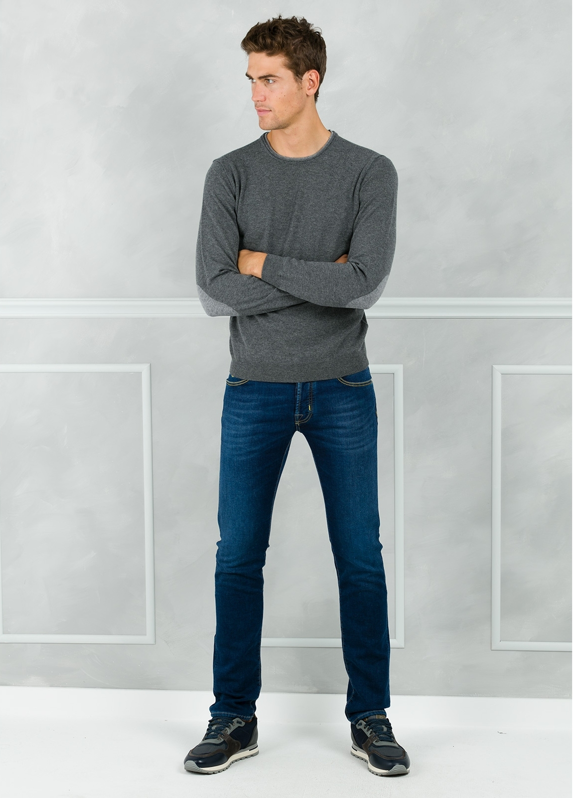 Jersey liso cuello redondo color gris con coderas en contraste. 100% Lana merino.