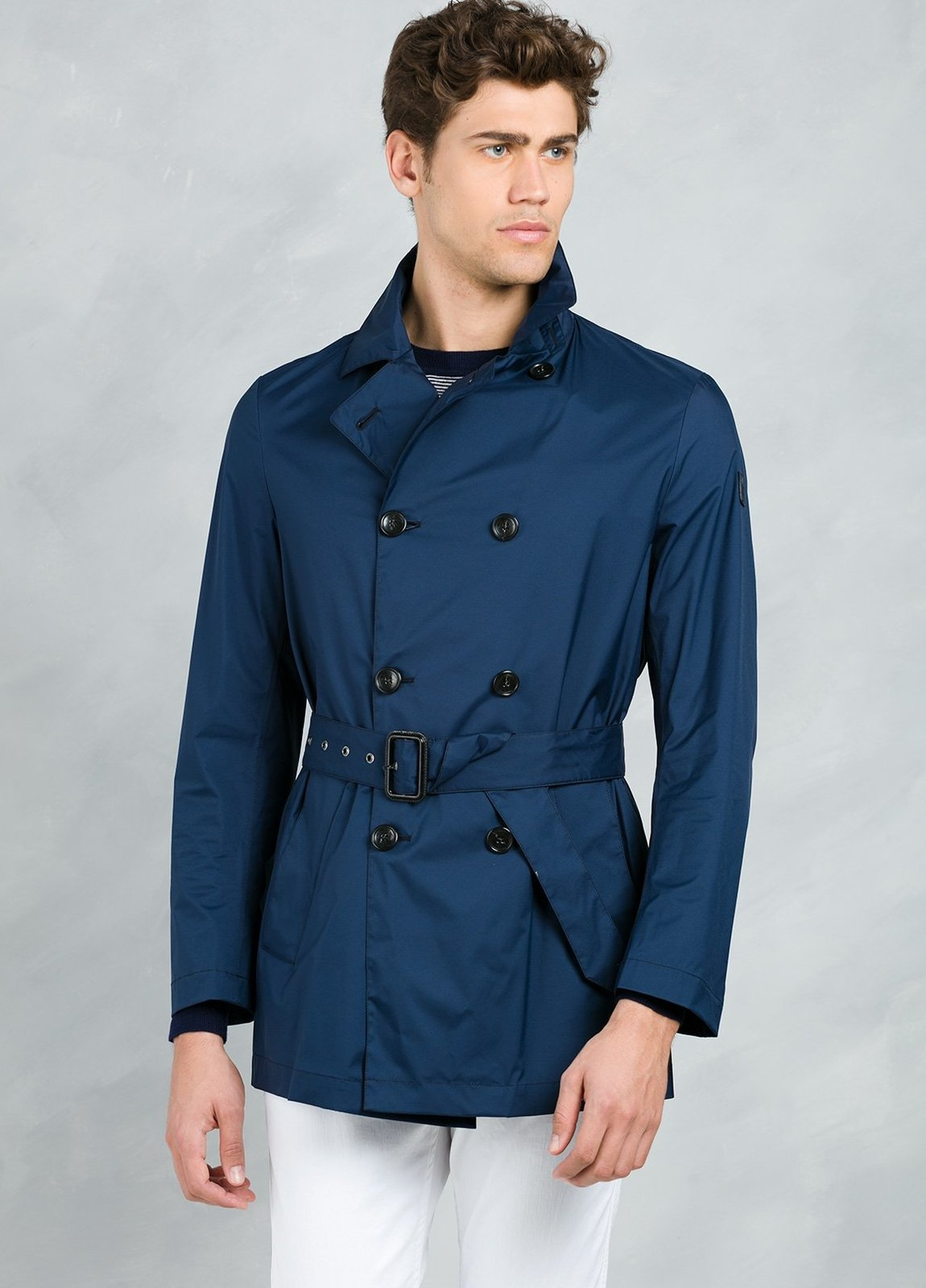 Gabardina corta cruzada con botones y cinturón , color azul.