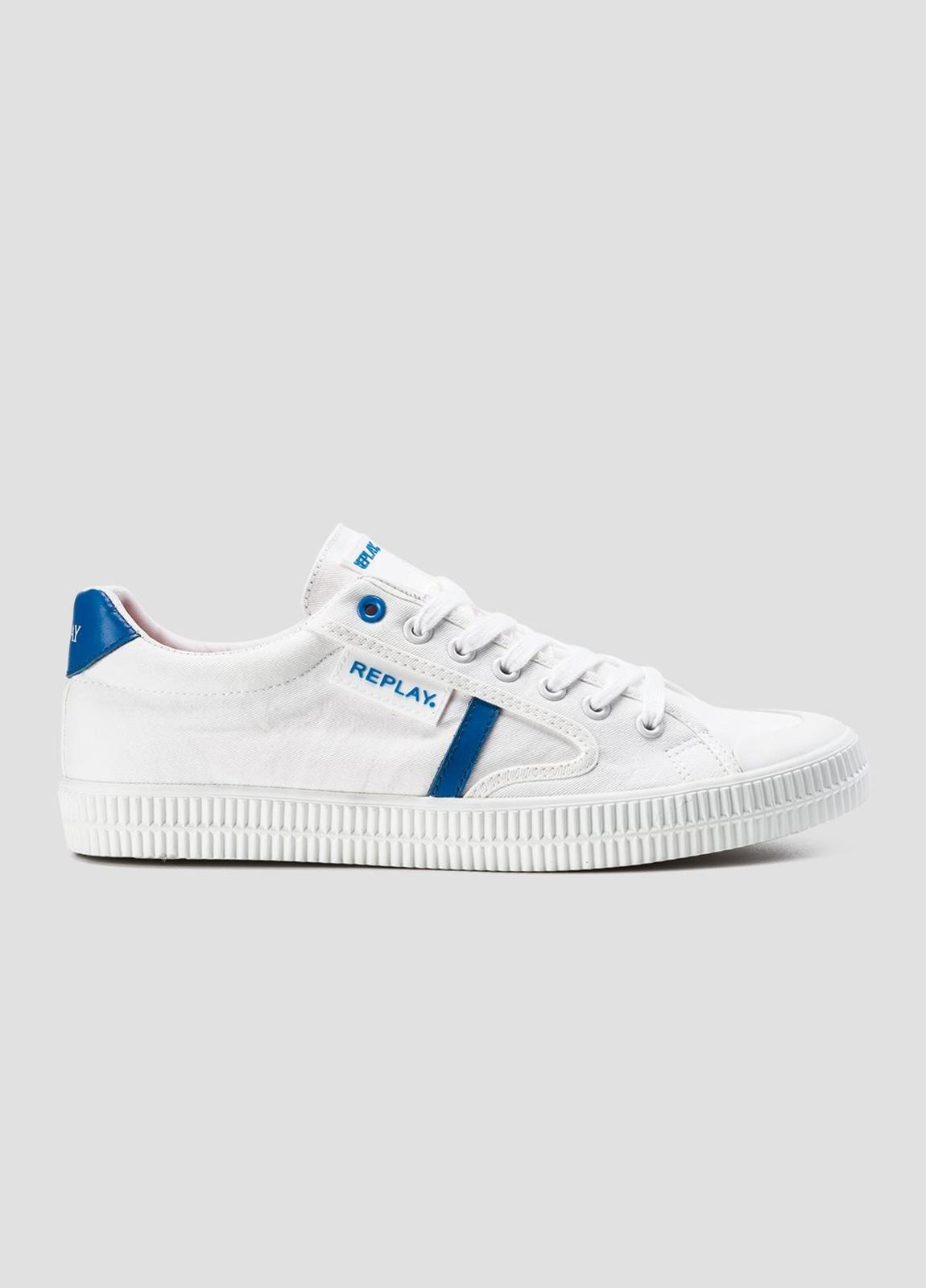 Calzado sport modelo MOSCOW con cordones color blanco con detalle azul. 100% Lona.