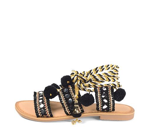 Ref. 3361 Sandalia plana con detalles etnicos. Tira al tobillo en color blanco, negro y oro. Pompones negros.