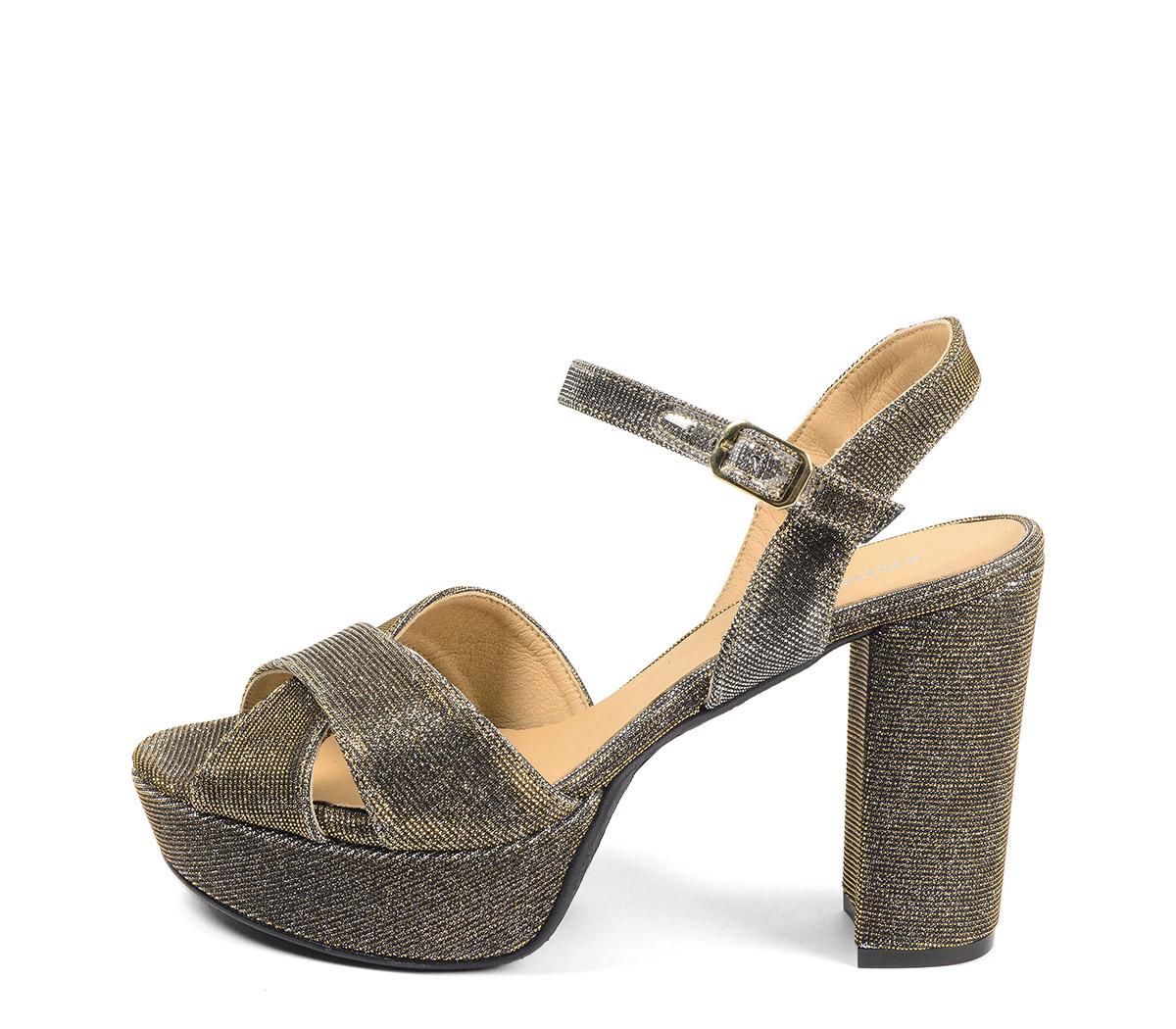 Ref. 4129 Sandalia brillante oro viejo con pala cruzada y pulsera al tobillo. Hebilla dorada. Tacón de 10.5 cm y plataforma delantera de 3 cm.