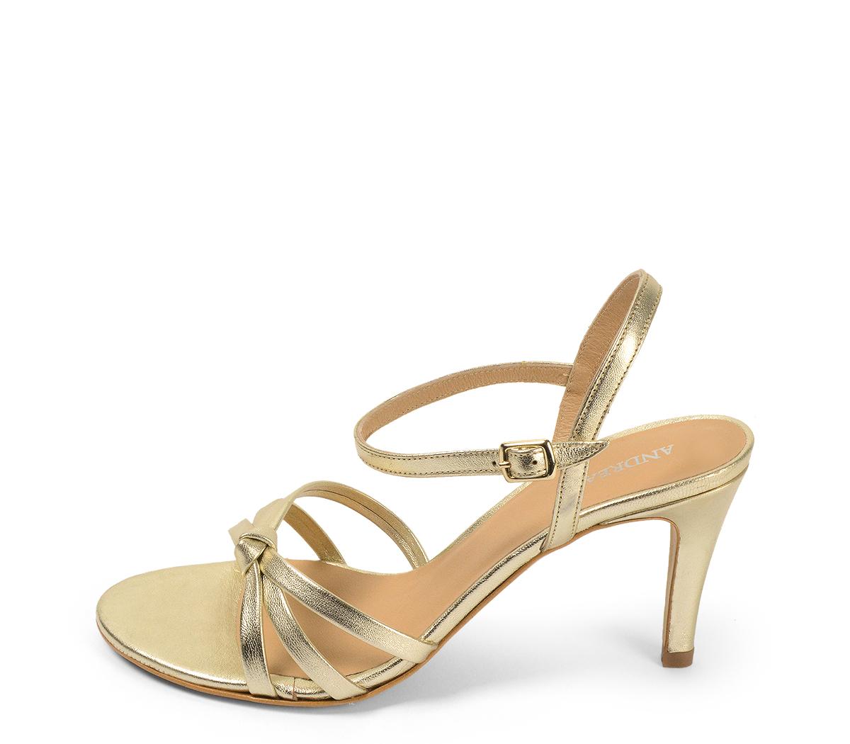 4247 Sandalia piel dorada con detalle nudo en la parte delantera y pulsera al tobillo con hebilla dorada. Altura tacón 8 cm y sin plataforma delantera.